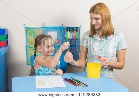 Five-year Girl Takes Pencil From Mother Hands
