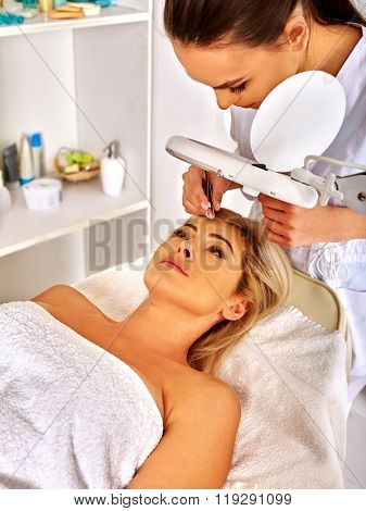 Lying woman middle-aged in spa salon with young beautician. Tweezing eyebrow by beautician.
