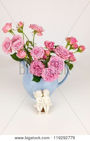 Pink flowers in blue jug. Roses in jug. Two angels on wooden bench. Vintage background. Shabby chic