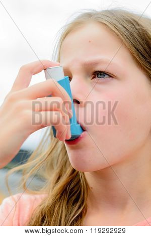 Girl Having Asthma Using The Asthma Inhaler