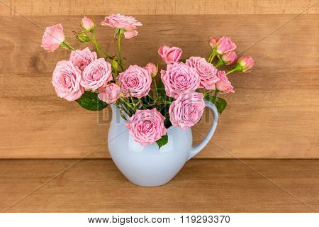 Pink flowers in blue jug. Roses in jug. Wooden background. Flowers in vase. Sha