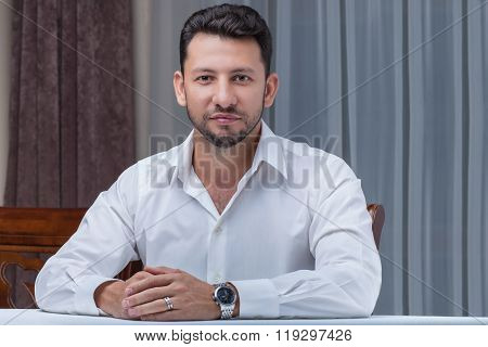 Young Man Sitting At Table