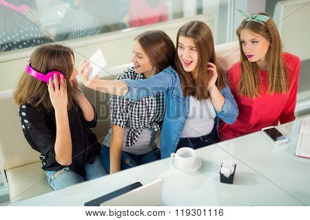 Portrait of four young women sitting at the table in the cafe take selfie with smart phone