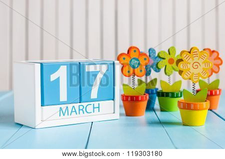 March 17th St. Patrick Day Concept. Image of march 17 wooden color calendar with flower on white bac
