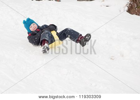 Cheerful Child Goes From The Snow Slides