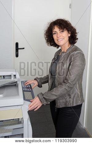 Pretty Happy Woman Using A Copy Machine At Work