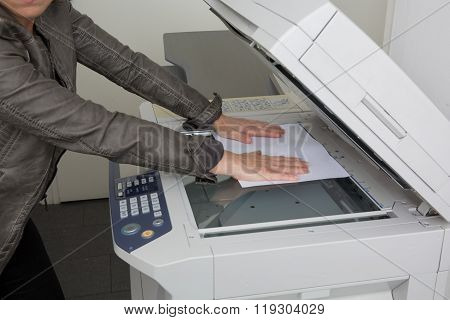 Business Woman Using  Photocopy Machine In Office