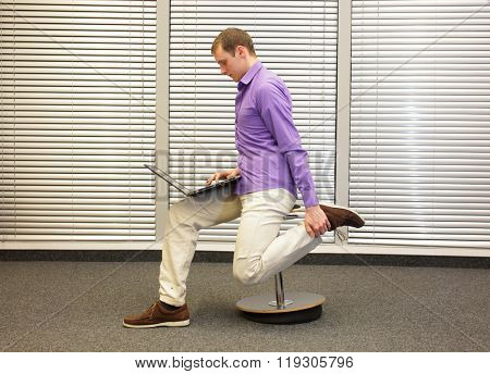 leg exercise during office work -  man sitting on pneumatic stool, working with laptop in his office