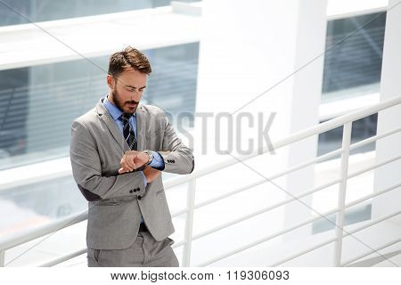 Handsome businessman looking on his luxury watches while standing in office interior