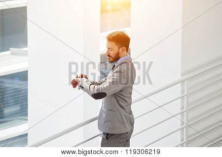 Confident businessman looking at watches on hand while standing inside his thriving company