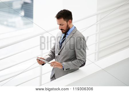 Successful man employer checking e-mail via digital tablet while standing in office interior