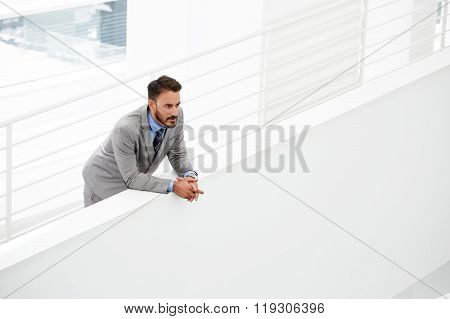 Thoughtful young male CEO thinking about growth his career while standing in modern office hallway