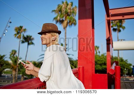 Attractive female listening radio via mobile phone during rest outside in summer day