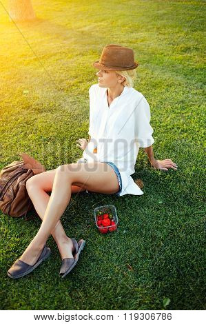 Young woman traveler with backpack admires something while sitting on a green grass lawn