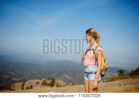 Blonde female looking away while standing on a high mountain in sunny day