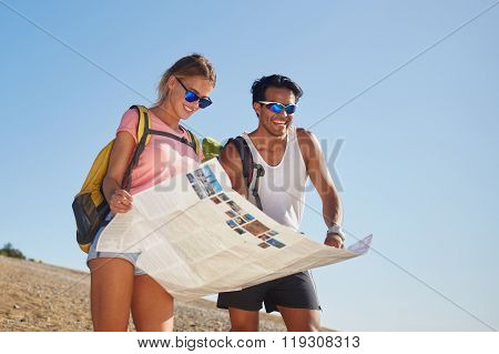Smiling happy man and woman travelers studying map to continue walking in the mountains in sunny day