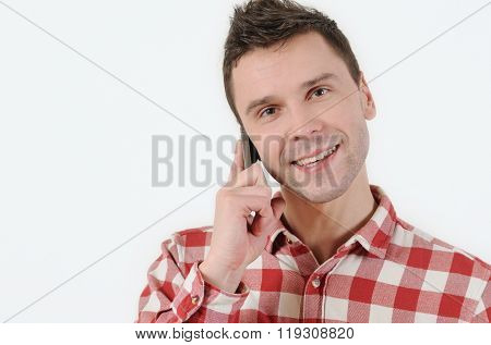 Handsome Man Talking On His Mobile Phone And Looking At Camera On White Background