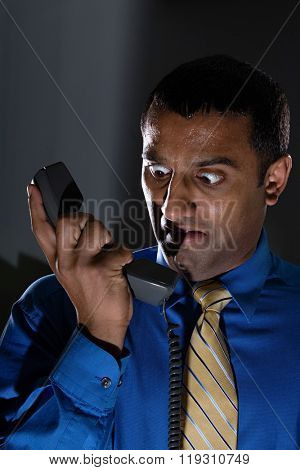 Terrified man looking at telephone