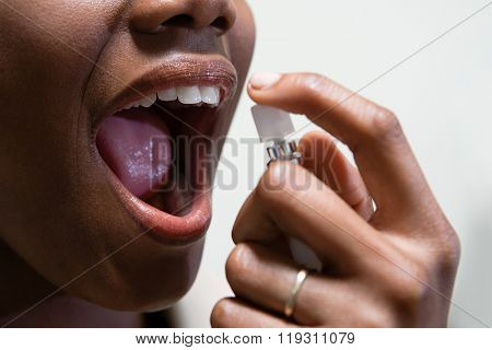Woman using breath freshener