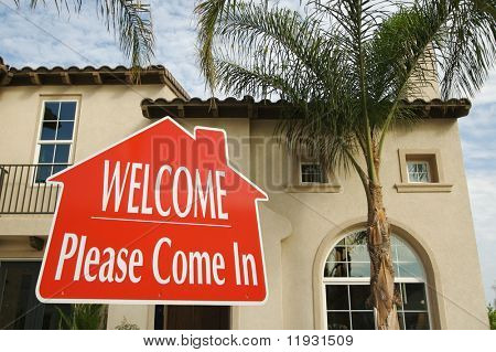 Welcome, Please Come In Real Estate Sign with new home in the background.