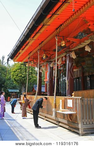 KYOTO, JAPAN - APRIL 2015 : People praying at Yasaka Shrine in the Gion District of Kyoto, Japan on April 15, 2015. The praying consists of ringing the bell, bowing, clapping hands, bowing again