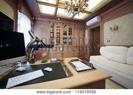 Interior of the modern cabinet in the English style with desktop, wooden bookcase and white sofa