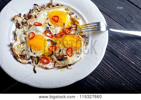 Close up of roasted eggs with onion and chilli