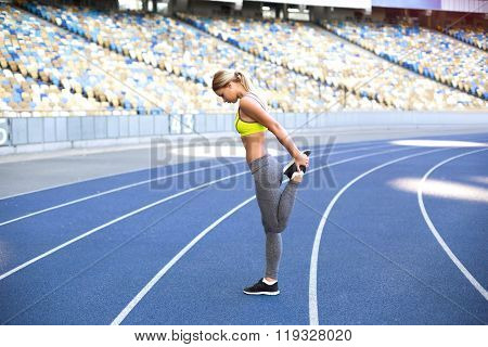 Young sportswoman is at large modern stadium