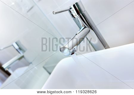 Running Water Of A Modern Faucet In The Washroom With Washstand Next To The Mirror