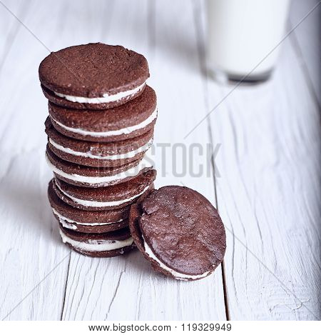 Chocolate sandwich cookies with cream filling on wood background.