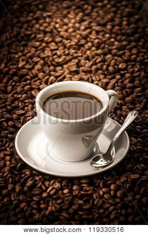 Black coffee on beans background with spoon