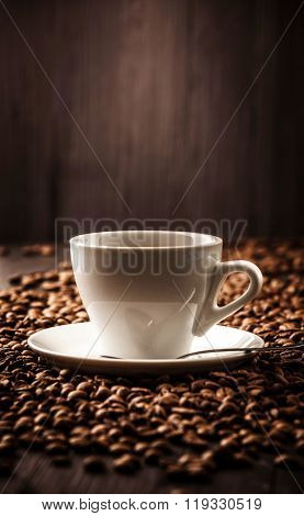 Cup fragrant coffee on beans background with spoon