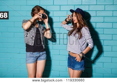 Happy Young People With Photo Camera Having Fun In Front Of Blue Brick Wall