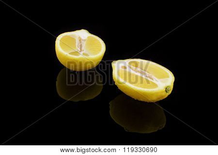 Divided Lemon With Drops On Black Background