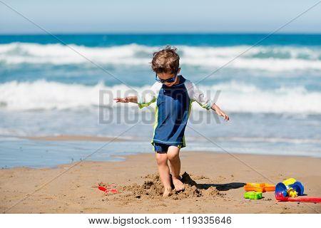 Little Boy Demolishing Sand Castle