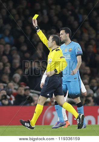 LONDON, ENGLAND - FEBRUARY 23: Referee Cuneyt Cakir shows a yellow card during the Champions League match between Arsenal and Barcelona at The Emirates Stadium