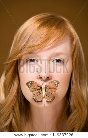 Butterfly covering woman's mouth