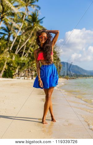 Beautiful Teenage Black Girl In Blue Skirt And Pink Bra On The Beach.