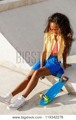 Beautiful Teenage Black Girl In Blue Skirt Sit With Her Penny Longboard.