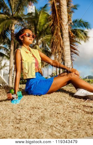 Beautiful Teenage Black Girl In Blue Skirt Sit With Her Penny Longboard Under The Palm Trees.