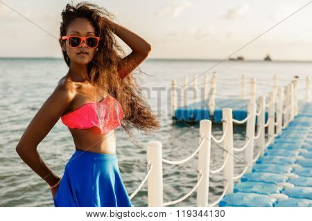 Beautiful Teenage Black Girl In Blue Skirt On Plastic Pier.