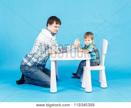 Funny Father And Little Son Competing In Arm Wrestling On Blue Background