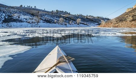 winter canoe paddling - boat bow and partially frozen lake - Horsetooth Reservoir near Fort Collins in Colorado
