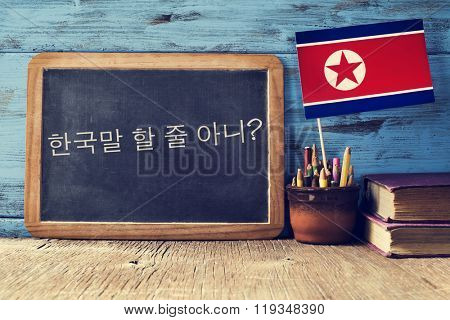 a chalkboard with the question do you speak korean? written in korean, a pot with pencils, some books and the flag of North Korea, on a wooden desk