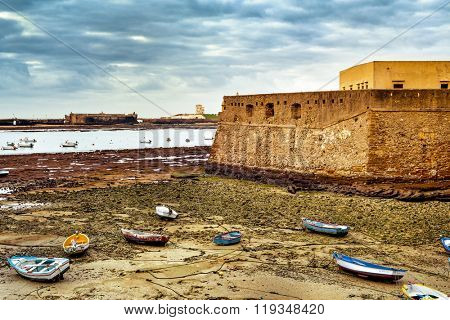 view of La Caleta Beach in Cadiz, with the Castle of Santa Catalina in the foreground ant the Castle of San Sebastian in the background