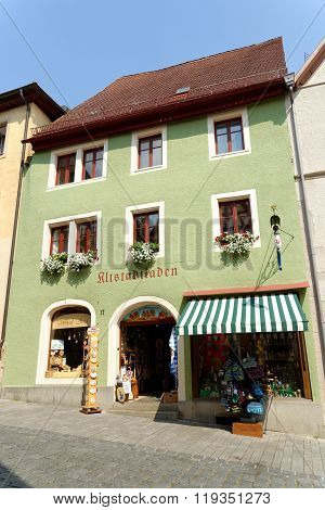 ROTHENBURG OB DER TAUBER GERMANY - AUGUST 10 2015: A traditional house and a souvenir shop in Rothenburg one of the best-preserved medieval towns in Europe part of the famous Romantic Road.