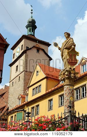 Rothenburg ob der Tauber in Germany. The White tower and the Seelbrunnen fountain on Chapel square. It embodies the Greek goddess Minerva the goddess of wisdom and patroness of the city.