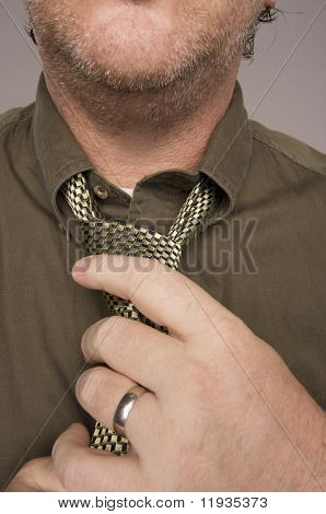 Man Fixing Tie Against Grey Background