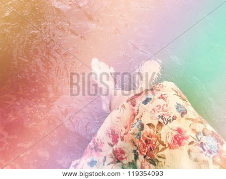 Women In Flowers Dress Sit And Dip Feet In Water