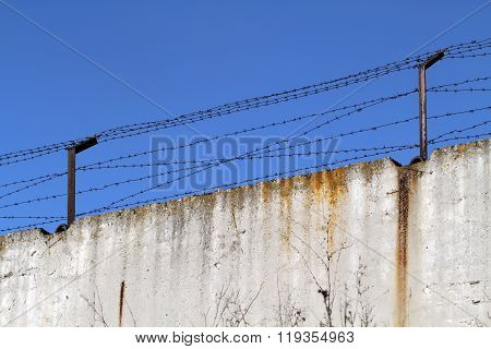 Concrete Fence With Barbed Wire On The Background Of Bright Blue Spring Sky.